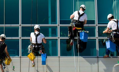 4 workers in harnesses cleaning office block windows