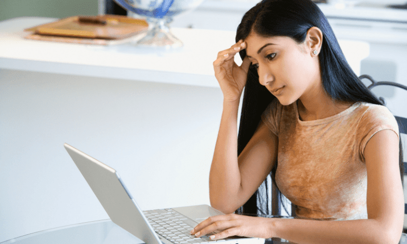 woman sitting at desk completing stress self assessment questionnaire on laptop