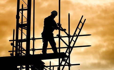 worker at the top of a structure holding unto scaffolding