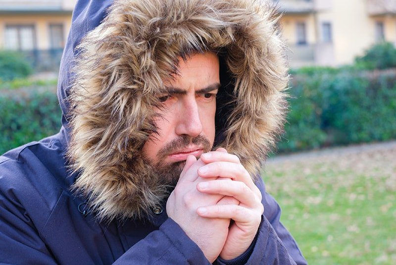 person wearing warm clothing outside and blowing into hands due to cold