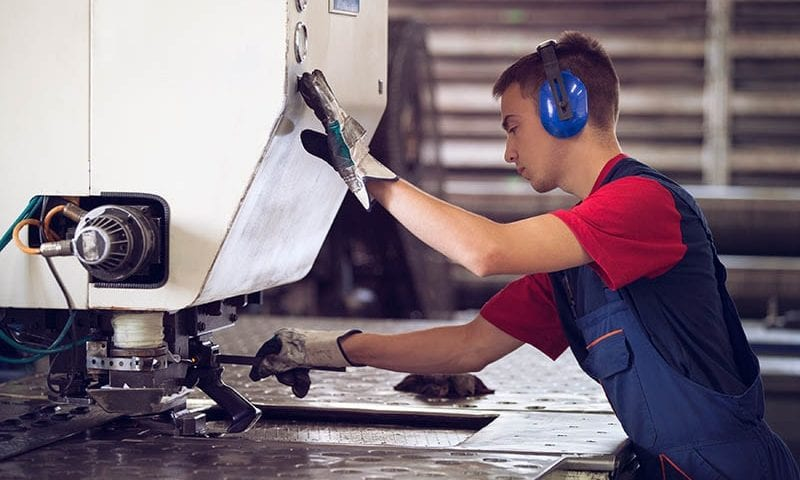 operator using a metal press following a safe system of work procedure
