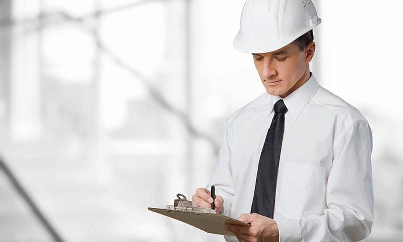 health and safety inspector writing on clipboard
