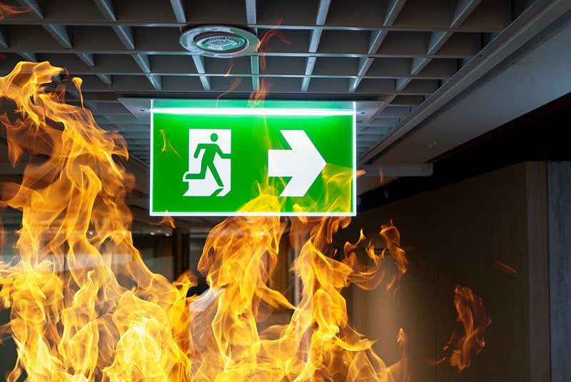 Green fire escape sign hang on the ceiling in an office