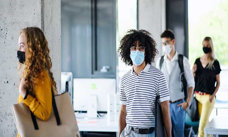 Young people with face masks back at work in office after coronavirus lockdown
