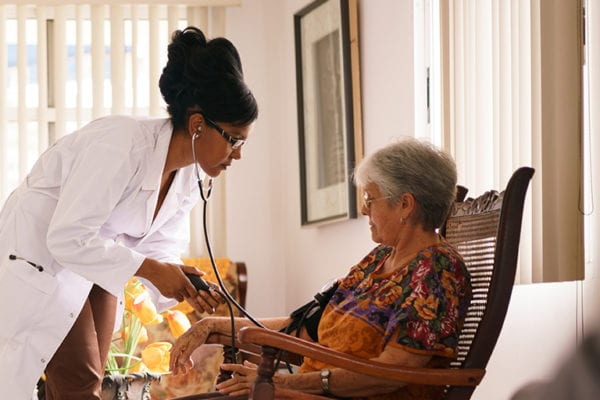 checking the blood pressure of elderly