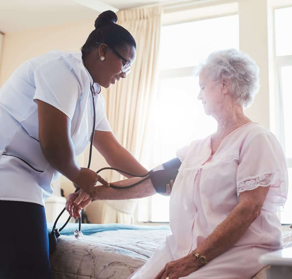 smiling nurse checking the blood pressure of the elderly